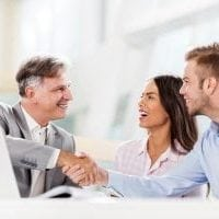 Happy insurance agent shaking hands with young man who came with his girlfriend.